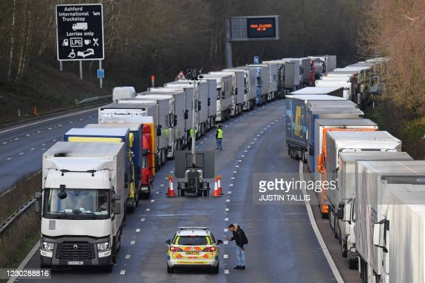 Police speak with a driver as freight lorries remain queued up on the M20 motorway, southbound, leading to the Port of Dover at Mersham in south east...