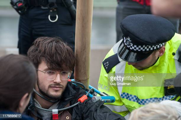Police speak with an activist locked to a wooden scaffold on October 7 2019 in London England Extinction Rebellion occupy several sites around...