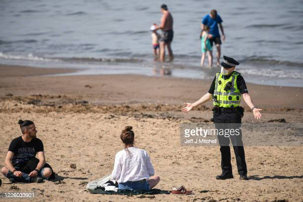Police speak with members of the public as they enjoy the hottest day of the year on May 20 2020 in Edinburgh Scotland The British government has...