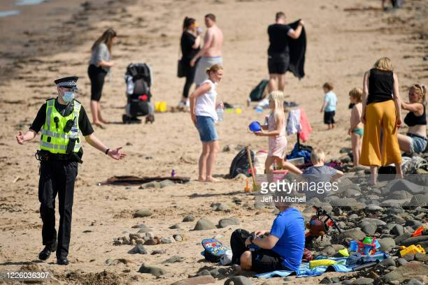 Police speak with members of the public as they enjoy the hottest day of the year on May 20, 2020 in Edinburgh, Scotland. The British government has...