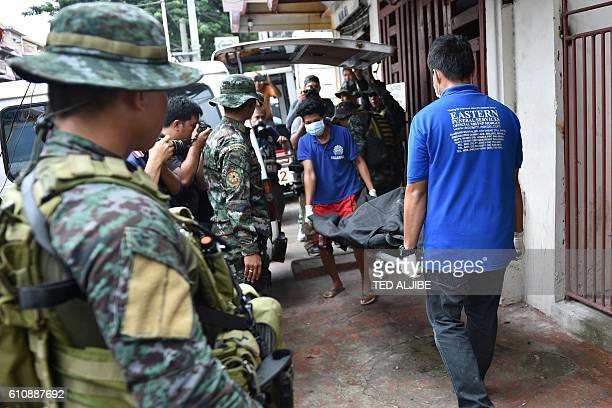 Police special action force personnel look on as funeral parlor workers carry the body of drug convict Peter Co who was killed in a knifing incident...