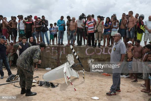Police specialists and the local population observe part of the helicopter propeller in Recife Northeast Brazil on January 23 2018 A helicopter from...