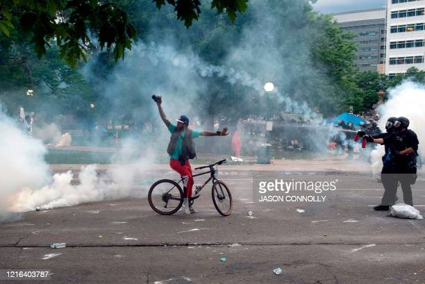 Police spray pepper spray at a demonstrator as he holds up his hands during a protest in Denver Colorado on May 30 over the death of George Floyd an...