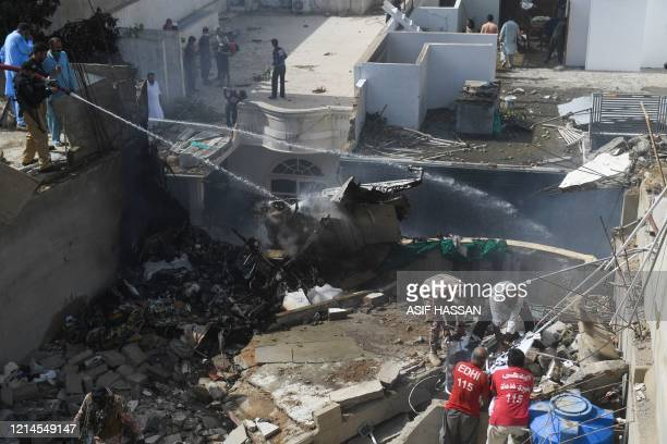 Police spray water on the part of a Pakistan International Airlines aircraft after it crashed at a residential area in Karachi on May 22 2020 A...