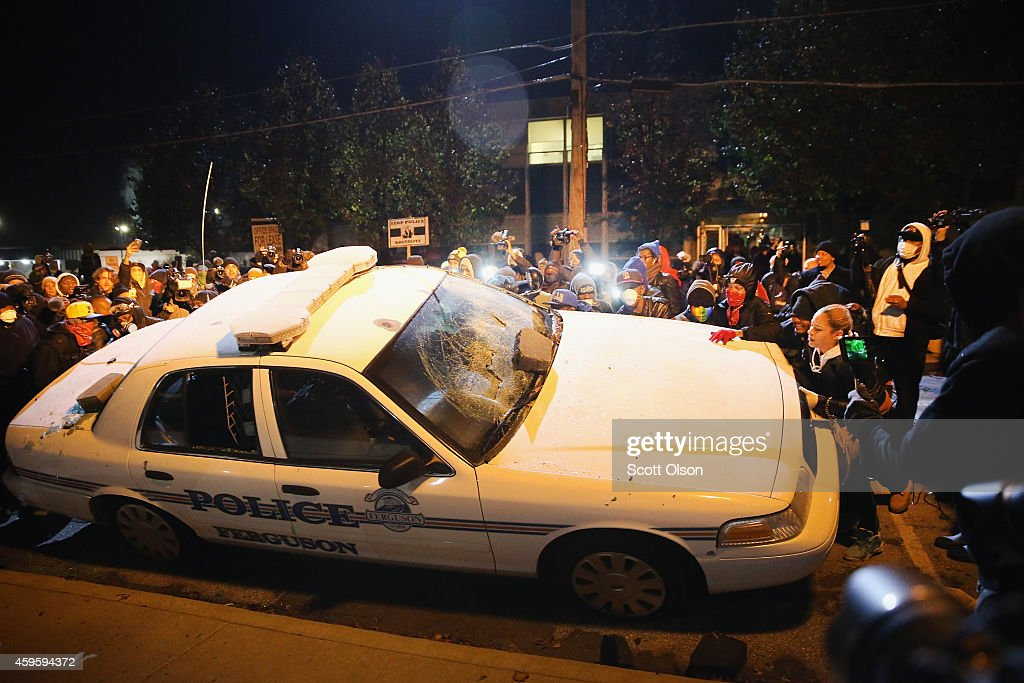 A police squad car is turned over by demonstrators during a protest on November 25, 2014 in Ferguson, Missouri. Yesterday protesting turned into rioting following the grand jury announcement to not indict officer Darren Wilson in the Michael Brown case. Brown, an 18-year-old black man, was killed by Darren Wilson, a white Ferguson police officer, on August 9. At least 12 buildings were torched and more than 50 people were arrested during the night-long rioting.