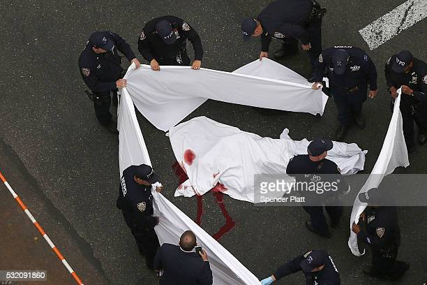 Police stand around the body of a man killed in a police involved shooting in midtown Manhattan on May 18 2016 in New York City The knifewielding man...