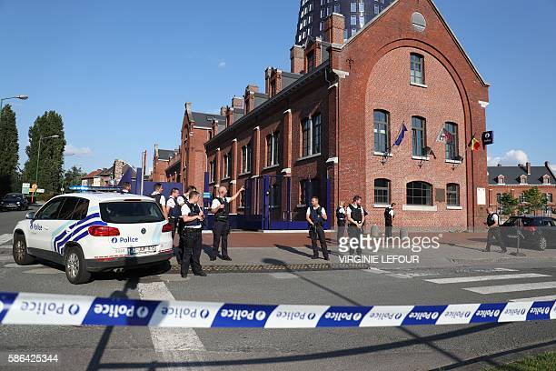 Police stand as they secure the area around a police building in the southern Belgian city of Charleroi following a machete attack on August 6 2016...