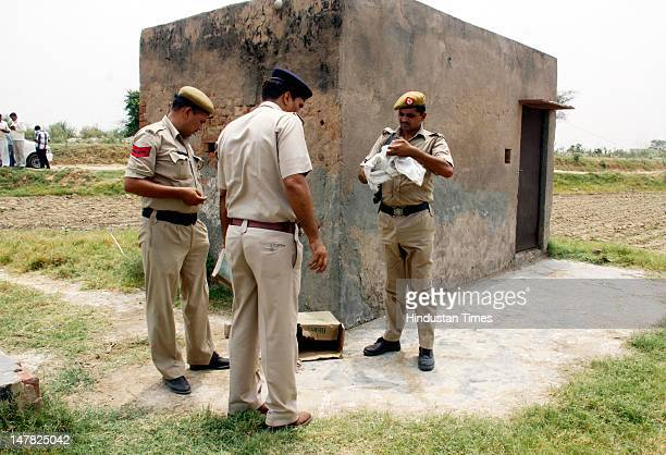 Police stand at a spot where Gurgaon police claim to killed one gangster Virendar aka Kana in an encounter at Dhankot on July 4 2012 in Gurgaon India...