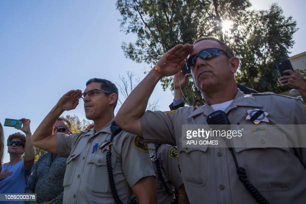 Police stand at attention as a motorcade carrying Ventura Country sheriff Sgt Ron Helus who was killed in a shooting at Borderline Bar the night...