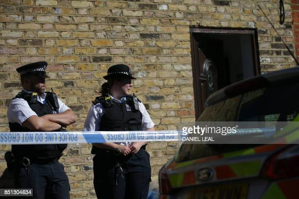 Police stand at the entrance to a property where the charred remains of a body were found in the back garden in Southfields southwest London on...