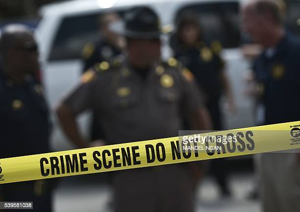 Police stand behind a crime scene tape near the mass shooting at the Pulse nightclub on in Orlando Florida on June 12 2016 A somber President Barack...