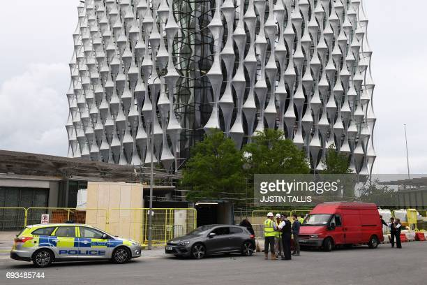 Police stand beside two vehicles in which they carried out controlled explosions near the new but still unoccupied US embassy building in south...