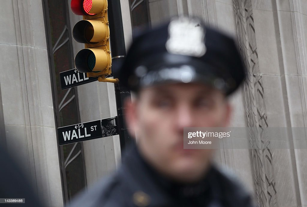 Police stand by as protesters march to Wall Street during an ACT-UP and Occupy Wall Street demonstration on April 25, 2012 in New York City. ACT-UP (AIDS Coalition to Unleash Power), was marking their 25-year anniversary in supporting services for people with AIDS worldwide. They were joined by Occupy Wall Street protesters in a march from New York's city hall to Wall Street. The groups called for a tax on Wall Street transactions and speculative trades to raise money for to end the global AIDS epidemic and provide universal healthcare in the U.S.