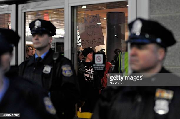 Police stand by at the doors as a small group of protestors occupies a space inside as thousands turn out for a January 29th 2017 Immigration Ban...