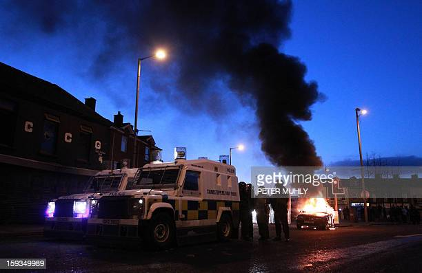 Police stand by their armoured vehicles as a car burns following violence between loyalists nationalists and the police in east Belfast Northern...
