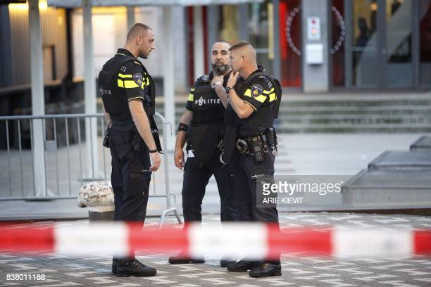 Police stand during the evacuation the Maassilo concert venue after a concert by Californian ban AllahLas was canceled in relation to a terror attack...
