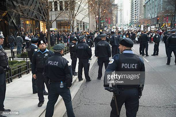 Police stand guard along the Michigan Avenue shopping district during a demonstration on December 9 2015 in Chicago Illinois About 1000 protestors...