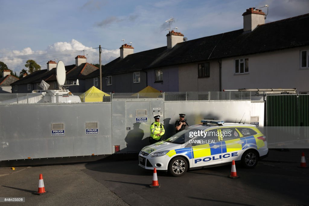 Police stand guard alongside a police barrier during a search operation by a police forensics team of a house in Sunbury, Surrey near London on September 17, 2017. Britain downgraded its terrorism threat level to severe from critical on September 17, 2017, after police made a second arrest in their investigations over the bombing of a London Underground train. / AFP PHOTO / Daniel LEAL
