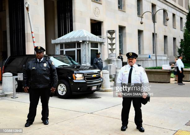 Police stand guard as a car departs the Department of Justice building in Washington, DC on November 7, 2018. - The US attorney general, Jeff...