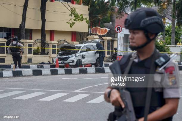 TOPSHOT Police stand guard as a car that was used to attack the police headquarters is examined in Pekanbaru on May 16 2018 Four men who attacked an...