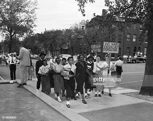 Police stand guard as a group of African American students escorted by Reverend James L Johnson march past two demonstrators protesting desegregation...