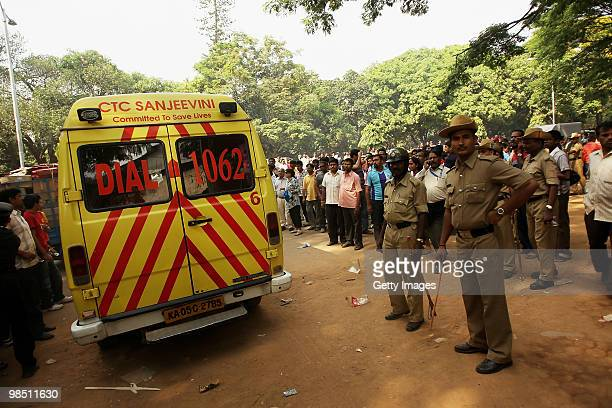 Police stand guard as a injured fan of the Challengers travels in an ambulance during the 2010 DLF Indian Premier League T20 group stage match...