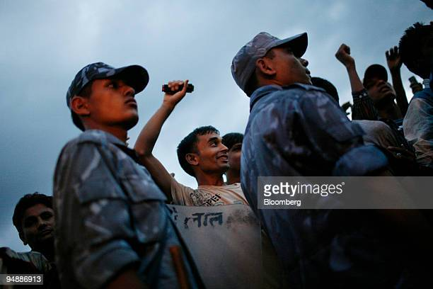 Police stand guard as anti-monarchy demonstrators cheer outside the Narayanhiti Royal Palace shortly after a news conference by former Nepali King...