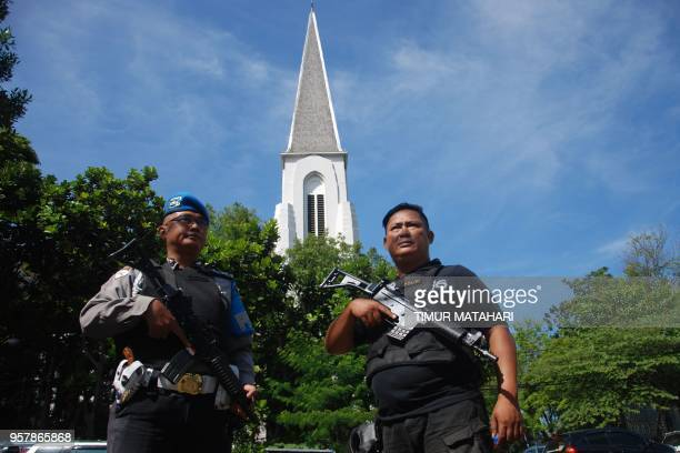 Police stand guard as Christian devotees attend a Sunday mass at the Saint Petrus church in Bandung on May 13 2018 A wave of blasts including a...
