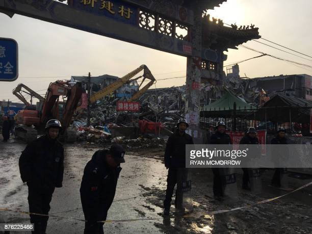 Police stand guard as demolition works take place at the site of a fatal housing block fire in Beijing on November 19 2017 Chinese authorities on...