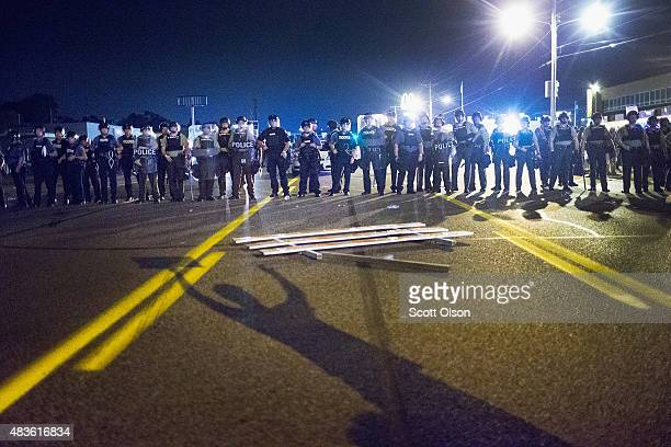 Police stand guard as demonstrators, marking the one-year anniversary of the shooting of Michael Brown, protest along West Florrisant Street on...