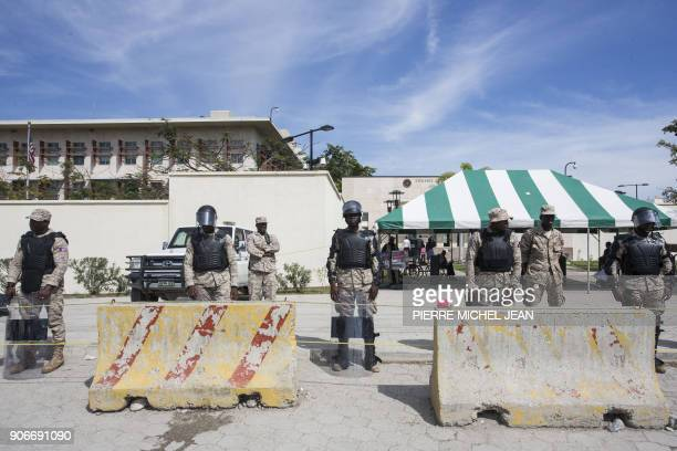 Police stand guard as Haitians gather in front of the US Embassy in PortauPrince during a sitin to express their dissatisfaction with the recent...