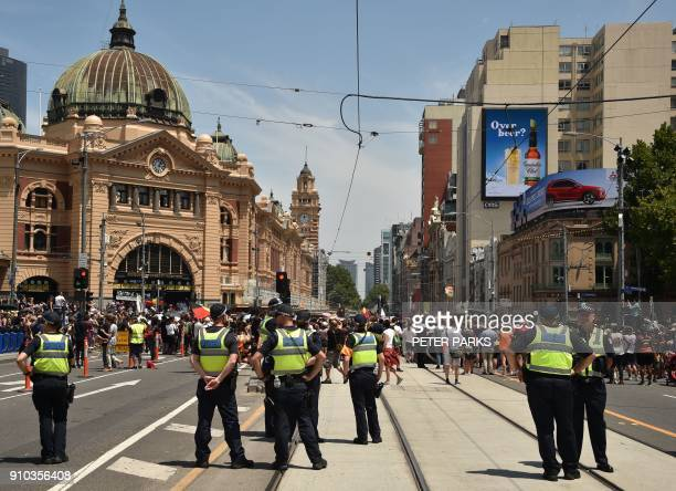 Police stand guard as participants take part in an 'Invasion Day' rally on Australia Day outside Flinders Street Station in Melbourne on January 26...