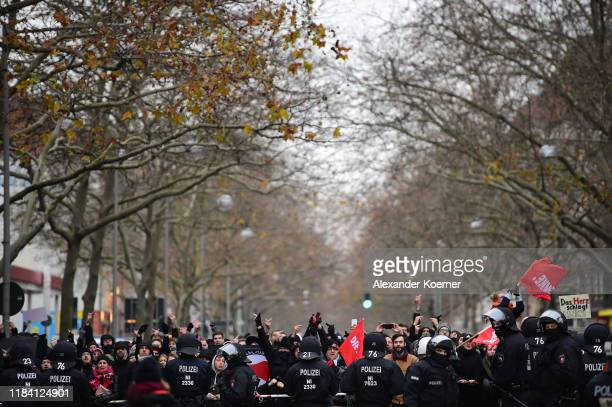 Police stand guard as protestors shout slogans towards Neo-Nazis and right-wing supporters during a march to voice their anger at the reporting by...