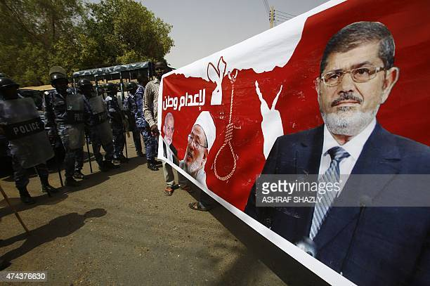 Police stand guard as Sudanese Islamists hold a poster bearing portraits of Egypt's ousted president Mohamed Morsi Egyptian Muslim Brotherhood leader...