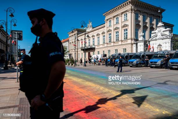 Police stand guard as the street is painted in rainbow colors ahead a demonstration against the 'LGBT' rights movement in Warsaw, on August 16, 2020.