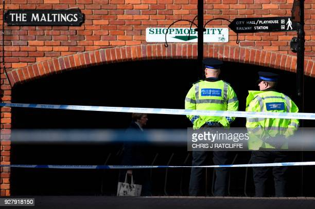 Police stand guard at a cordon at the scene at The Maltings shopping centre in Salisbury southern England on March 6 2018 where a man and a woman...