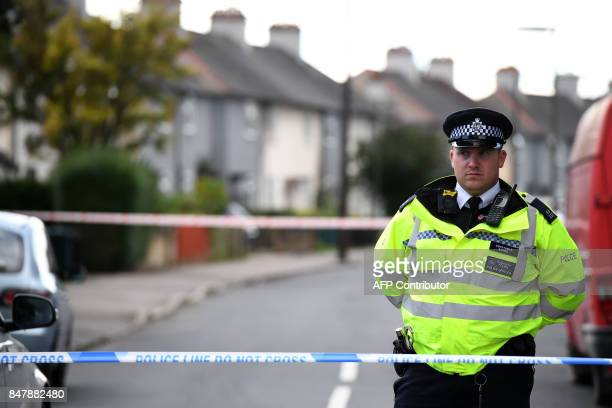 Police stand guard at a cordon during a raid on a home in Sunbury Surrey near London on September 16 2017 British police raided a home near London on...