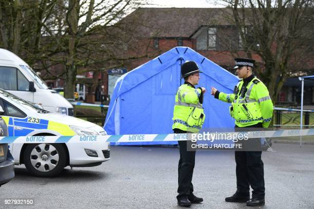 Police stand guard at a cordon in front of a police tent at the scene at The Maltings shopping centre in Salisbury southern England on March 6 2018...