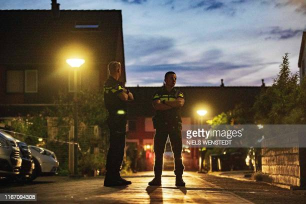 Police stand guard at a home during investigation after a shooting incident in which several victims were killed, on the Heimerstein in Dordrecht, on...