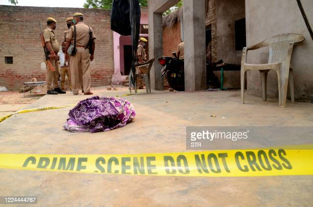 TOPSHOT Police stand guard at a site following an attack where eight policemen have been shot at Bikhru some 30 km from Kanpur on July 3 2020 Eight...