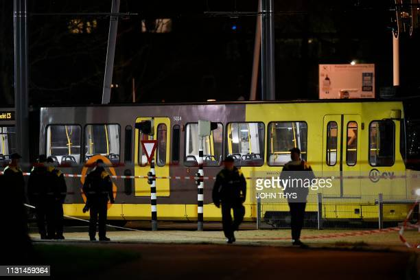 Police stand guard at the cordoned off area surrounding the tram where a gunman opened fire killing at least three persons and wounding several at...