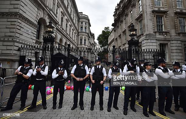 Police stand guard at the entrance to Downing Street in central London on July 8 following a protest British finance minister George Osborne will...