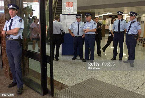 Police stand guard at the entrance to the Auckland District Court for the appearance of Mark Middleton who was charged with threating to kill Paul...