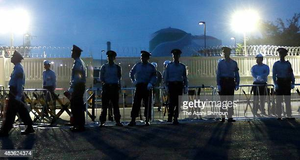 Police stand guard at the main gate of the Kyushu Electric Power Co Sendai Nuclear Power Plant as the utility activates the No 1 reactor on August 11...