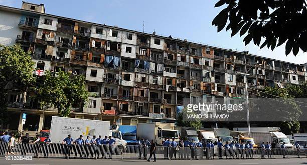 Police stand guard before the evacuation of members of the Georgian minority from Abkhazia and South Ossetia from a rundown former hotel in Tbilisi...