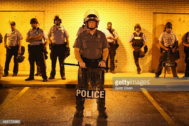 Police stand guard before the mandatory midnight curfew on August 16 2014 in Ferguson Missouri The curfew was imposed on Saturday in an attempt to...