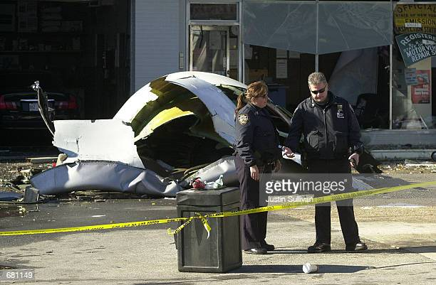 Police stand guard in front of the engine from American Airlines Flight 587 that crashed November 12, 2001 in Rockaway Beach, New York City. The...