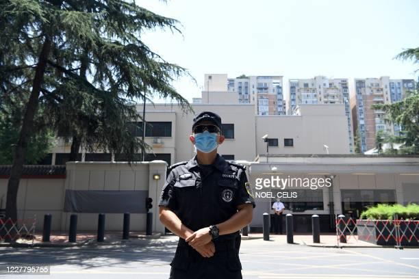 Police stand guard in front of the US Consulate in Chengdu, southwestern China's Sichuan province on July 27, 2020. - The American flag was lowered...