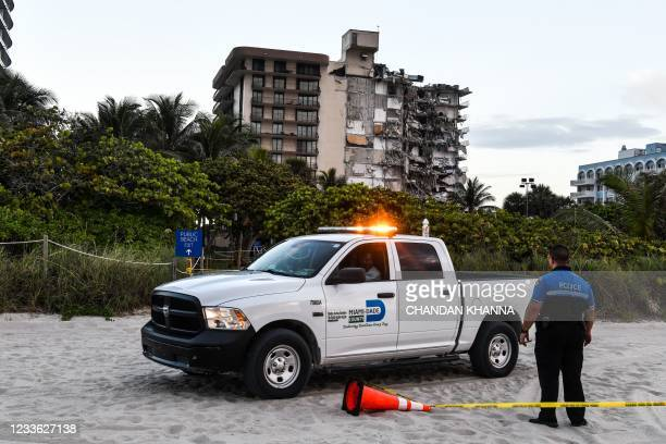 Police stand guard near a partially collapsed building a partially collapsed building in Surfside north of Miami Beach, on June 24, 2021. - The...