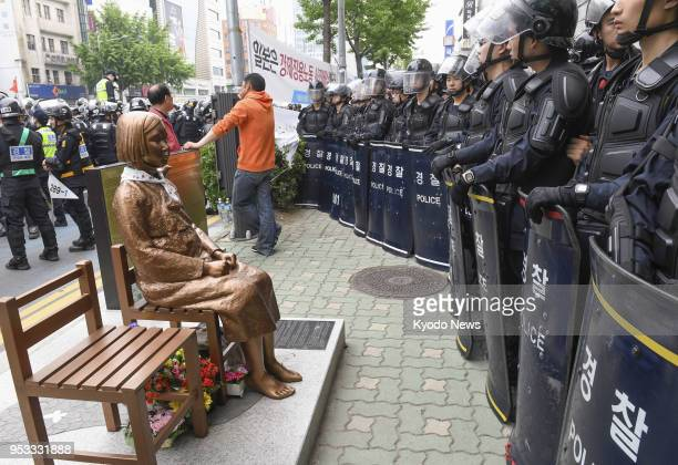 Police stand guard near a statue of a girl symbolizing the issue of wartime comfort women in front of the Japanese Consulate General in Busan on May...